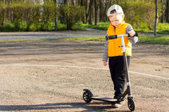 Handsome little boy with his scooter Royalty Free Stock Photos