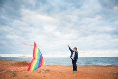 Handsome little boy holding flying kite on the overcast sea and sky background. In autumn Royalty Free Stock Photo