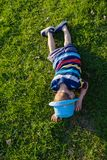 Handsome little boy lying on grass. Little dreamer lies in meadow with hat. Child in nature outside city. Carefree vacation. Handsome little boy lying on grass Royalty Free Stock Images