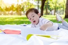 Handsome little boy is opening a book for reading and learning by himself at a park. Charming handsome kid love reading and lookin royalty free stock photo