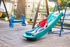 Handsome little boy plays on slide on playground Stock Photo