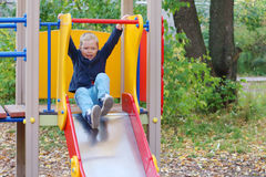 Handsome little boy plays on slide on playground Royalty Free Stock Images