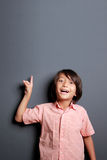 Handsome little boy pointing upwards Stock Images