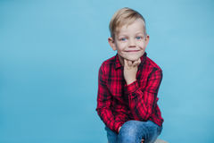Handsome little boy with red shirt. Fashion. Studio portrait over blue background. Fashionable little kid with red shirt. Fashion. Style. Studio portrait over royalty free stock photography