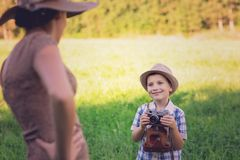 Handsome little boy with retro camera and girl model royalty free stock image