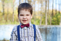 Handsome little boy in shirt and bow tie grimaces Stock Image