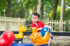 Handsome little boy in shirt plays on small carousel Stock Photo