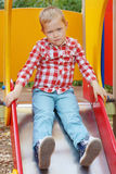Handsome little boy in shirt sits on slide Stock Photos