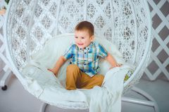 A beautiful little boy sits on a swing and poses for a photographer stock images