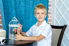 Handsome little boy is sitting at the table stock photos