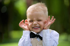 Handsome little boy in a suit to laugh outdoor. Handsome caucasian little boy in a suit to laugh and make fun Stock Photography