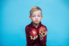 Handsome little boy with two red apples. Studio portrait over blue background Royalty Free Stock Image