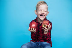 Handsome little boy with two red apples. Studio portrait over blue background Stock Photos