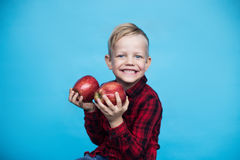 Handsome little boy with two red apples. Studio portrait over blue background Royalty Free Stock Photography