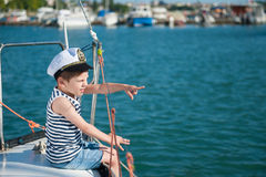 Handsome little captain boy pointing with his finger to the distance sitting on luxury yacht in summer tour. Handsome little captain boy pointing with his finger Royalty Free Stock Images