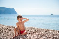 Handsome little boy watching far sitting on summer beach on tropic remote island Royalty Free Stock Images