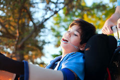 Handsome little disabled boy in wheelchair, enjoying sunset at p Stock Image