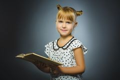 Handsome little girl with book smiling on gray background royalty free stock photos