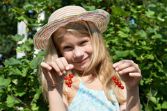 Handsome little girl with bunch of red currants Royalty Free Stock Photography