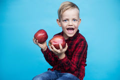 Handsome little kid with fruits. Studio portrait over blue background Royalty Free Stock Photo