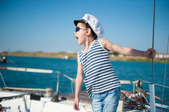Handsome little kid wearing sailor shirt and captain hat and sunglasses giving orders. Loudly shouting aboard royalty free stock photos
