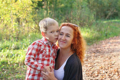 Handsome little son kisses his young mother. In autumn park at sunny day Royalty Free Stock Images