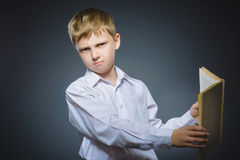 Handsome little stressed boy with book isolated on gray background stock photography