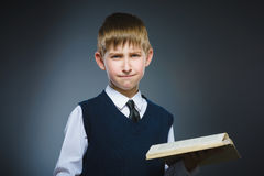 Handsome little stressed boy with book isolated on gray background stock image