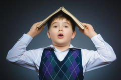 Handsome little stressed boy with book isolated on gray background royalty free stock photography