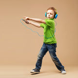 Handsome little stylish boy in headphones holding MP3 Player and Royalty Free Stock Photography