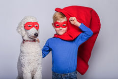 Handsome little superman with dog. Superhero. Halloween. Studio portrait over white background Stock Images