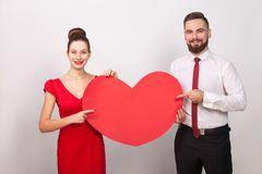 Handsome lively couple pointing finger at big heart, toothy smil. Ing. Indoor, studio shot,  on gray background Stock Images