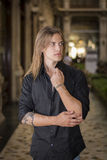 Handsome long hair young man indoors in elegant gallery. Handsome long hair man portrait in black shirt standing in elegant gallery in european city center Royalty Free Stock Photography