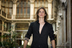 Handsome long hair young man indoors in elegant gallery. Handsome long hair man portrait in black shirt standing in elegant gallery in european city center Royalty Free Stock Photo