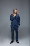 Handsome long haired man wearing stylish suit and looking away Royalty Free Stock Photography