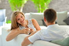 Handsome long haired young blonde woman sitting on a couch propped her head with one hand and holding a mug of delicious tea in an. Handsome long haired young Stock Photos