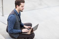 Handsome looking young Caucasian male typing on his fancy laptop. Sitting on concrete bleachers stairs outside Stock Photo