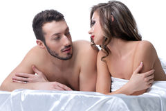 Handsome lovers talking in bed after sex Stock Images