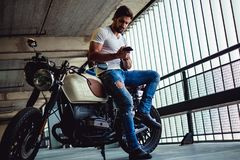 Handsome man sitting on his motorcycle and looking at phone. Handsome macho man with beard sitting on his motorcycle and looking at phone Royalty Free Stock Photo