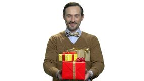 Handsome macho-man giving gift boxes. stock video