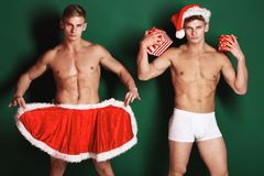 Handsome macho santa twins. Young handsome macho santa twins with sexy muscular athletic strong body has bare torso and strong belly in christmas cape or xmas Stock Photos