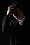 Handsome mafioso man touching hat in the dark Stock Photography
