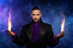 Handsome magician. Young brunette magician in stage costume performing flame tricks Royalty Free Stock Photos