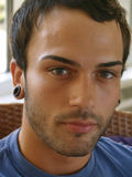 Handsome Male. Handsome, hip, unshaven young man with ear rings Stock Images