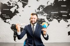 Male agent working at the travel agency office. Handsome male agent playing with globe and toy airplane at the travel agency office with world map on the Stock Image
