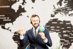 Male agent working at the travel agency office. Handsome male agent playing with globe and toy airplane at the travel agency office with world map on the Royalty Free Stock Photography