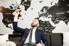 Male agent relaxing at the travel agency office. Handsome male agent playing with toy airplane at the travel agency office with world map on the background Stock Photography
