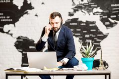 Male agent working at the travel agency office. Handsome male agent working with laptop at the travel agency office with map on the background Stock Images
