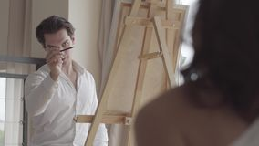 Handsome male artist painting beautiful half-dressed woman at home. Young pretty model posing for the man, who painting. A portrait. Art concept stock footage