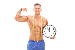 Handsome male athlete holding a big wall clock  background. Handsome male athlete holding a big wall clock and flexing his muscle isolated on white background Royalty Free Stock Images